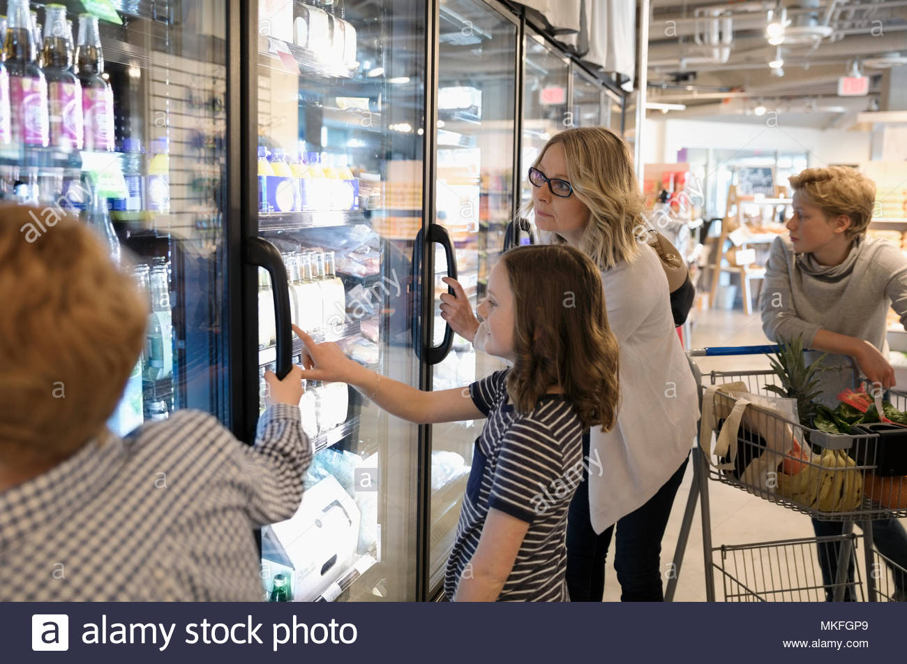 Mother and children grocery shopping in refrigerated market aisle - Stock Image