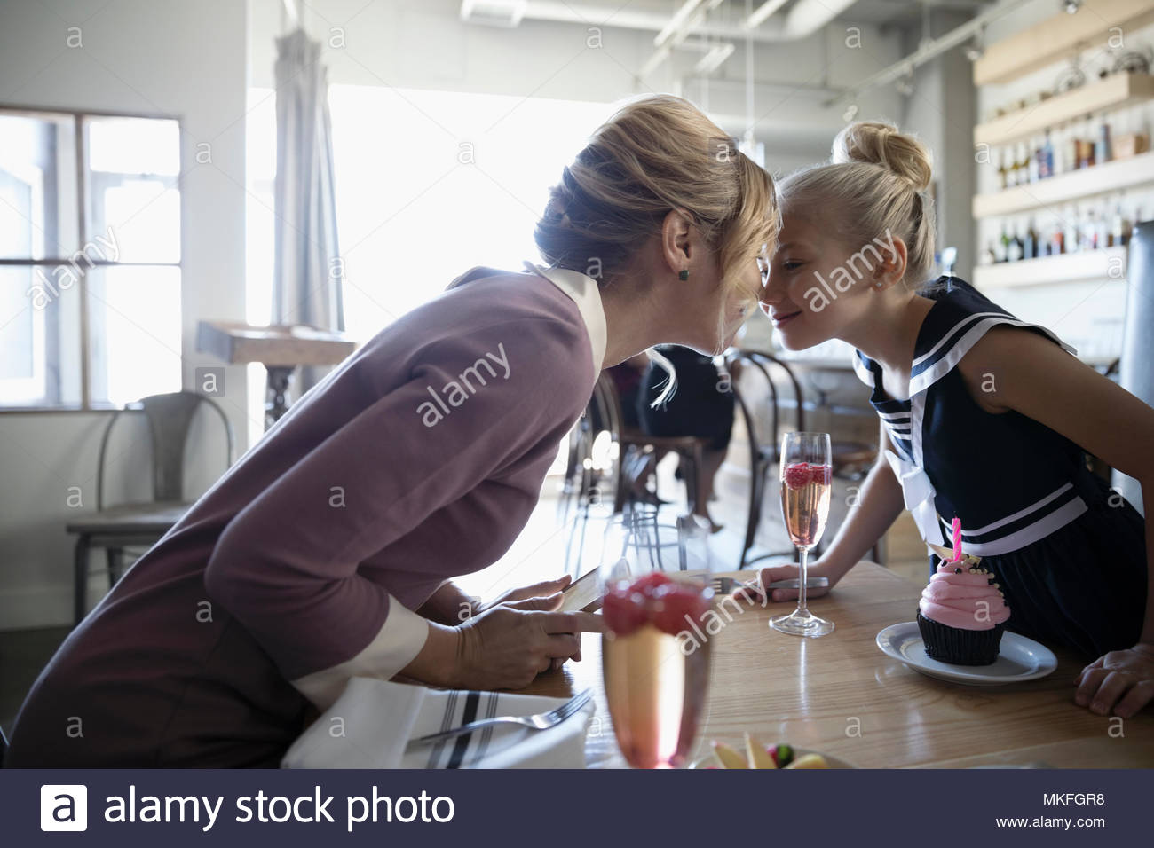Affectionate mother and daughter rubbing noses, celebrating birthday in cafe - Stock Image