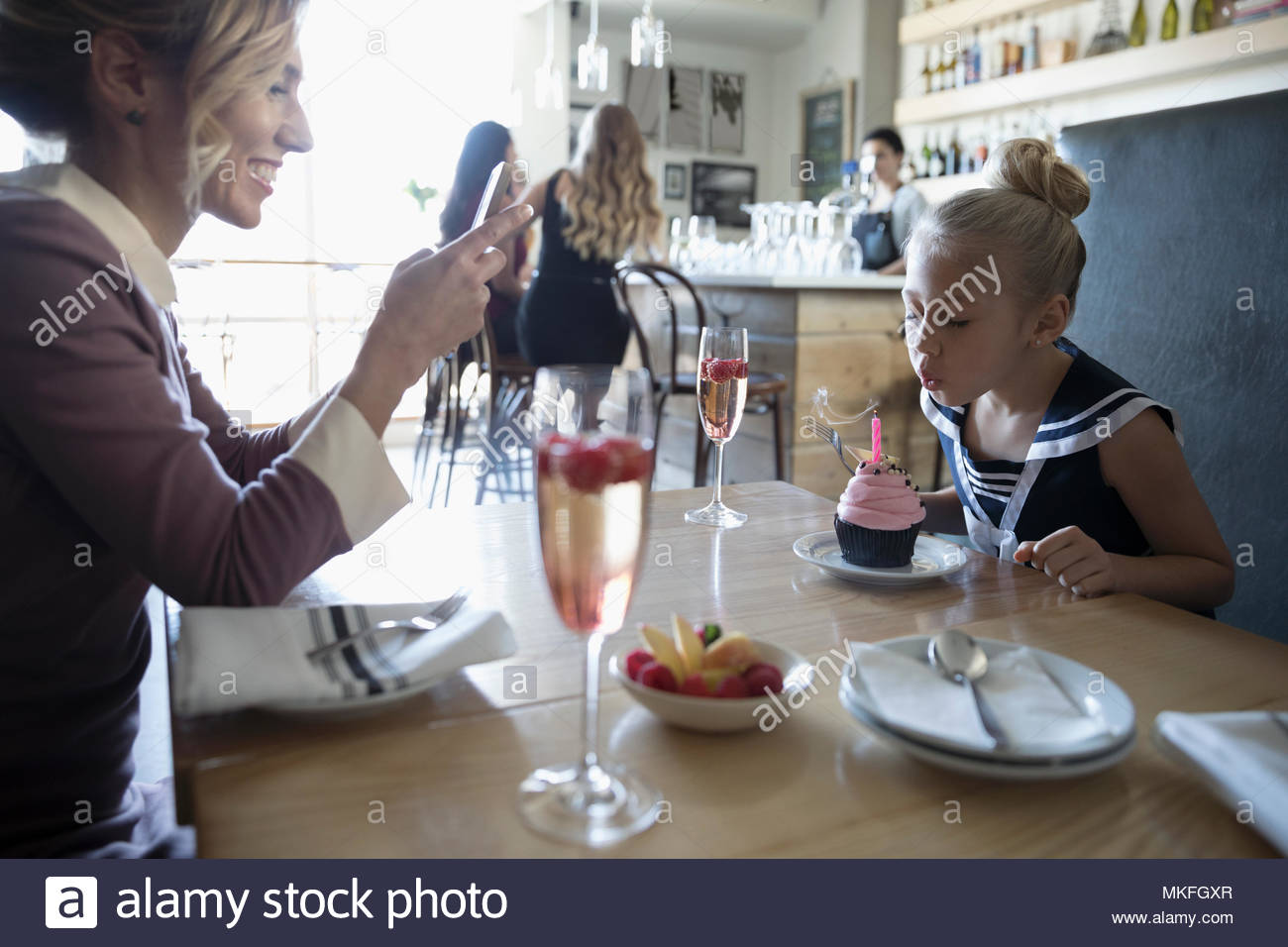 Mother with camera phone photographing daughter blowing out birthday candle on cupcake in cafe - Stock Image