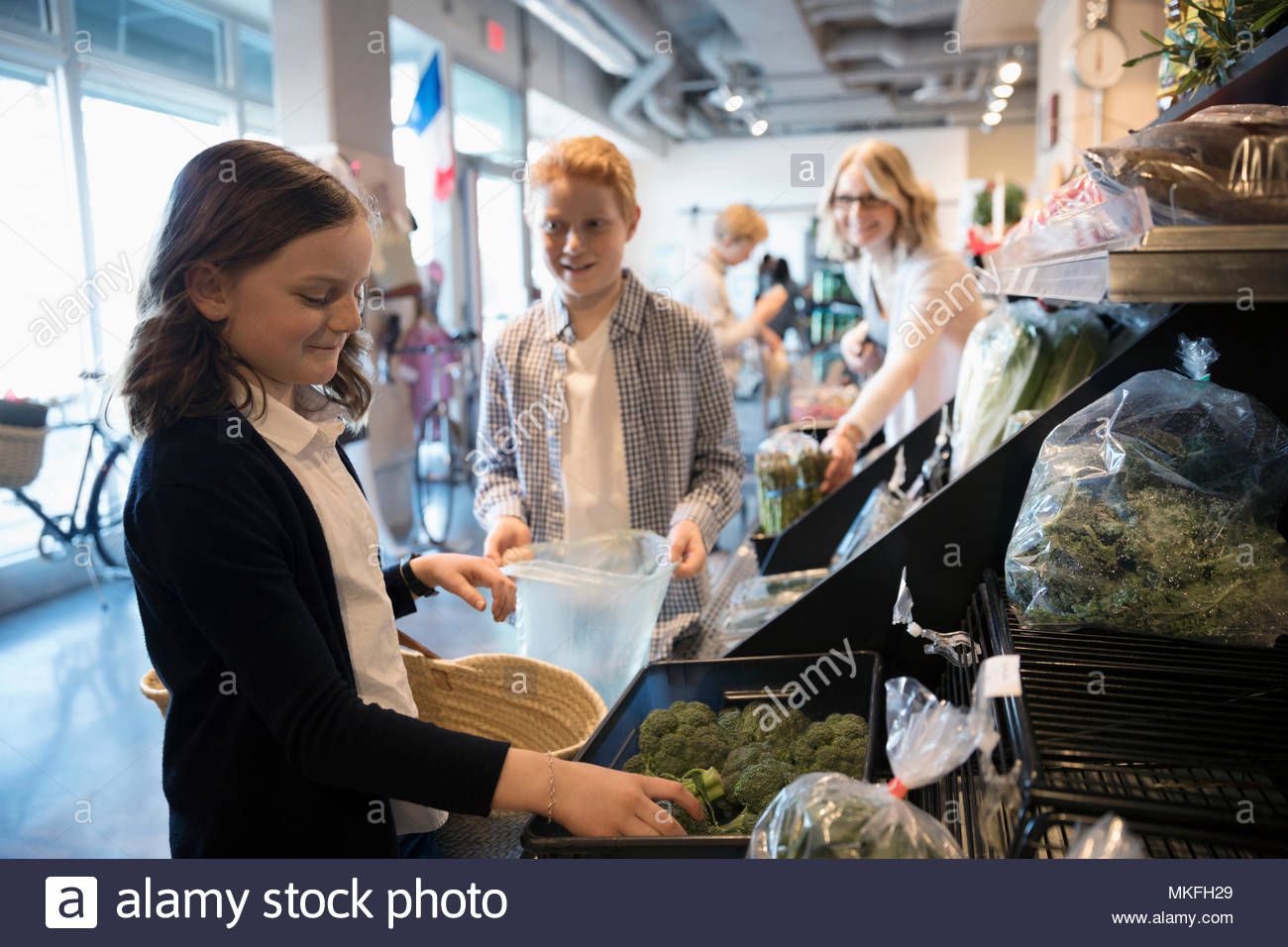 Girl grocery shopping with family, picking out broccoli in market - Stock Image