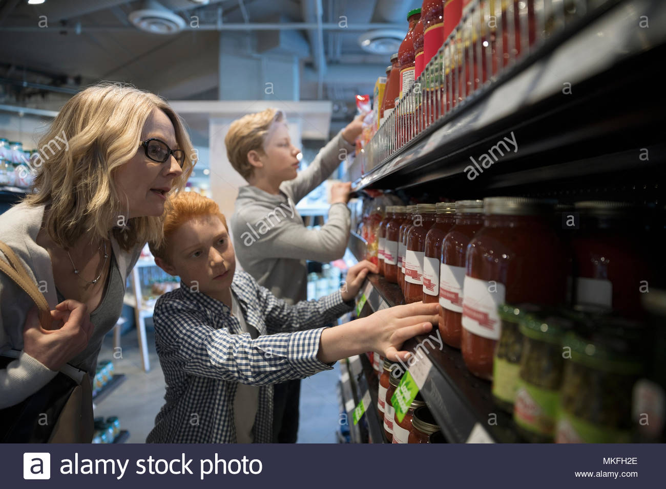 Mother and son grocery shopping, picking out spaghetti sauce in market - Stock Image