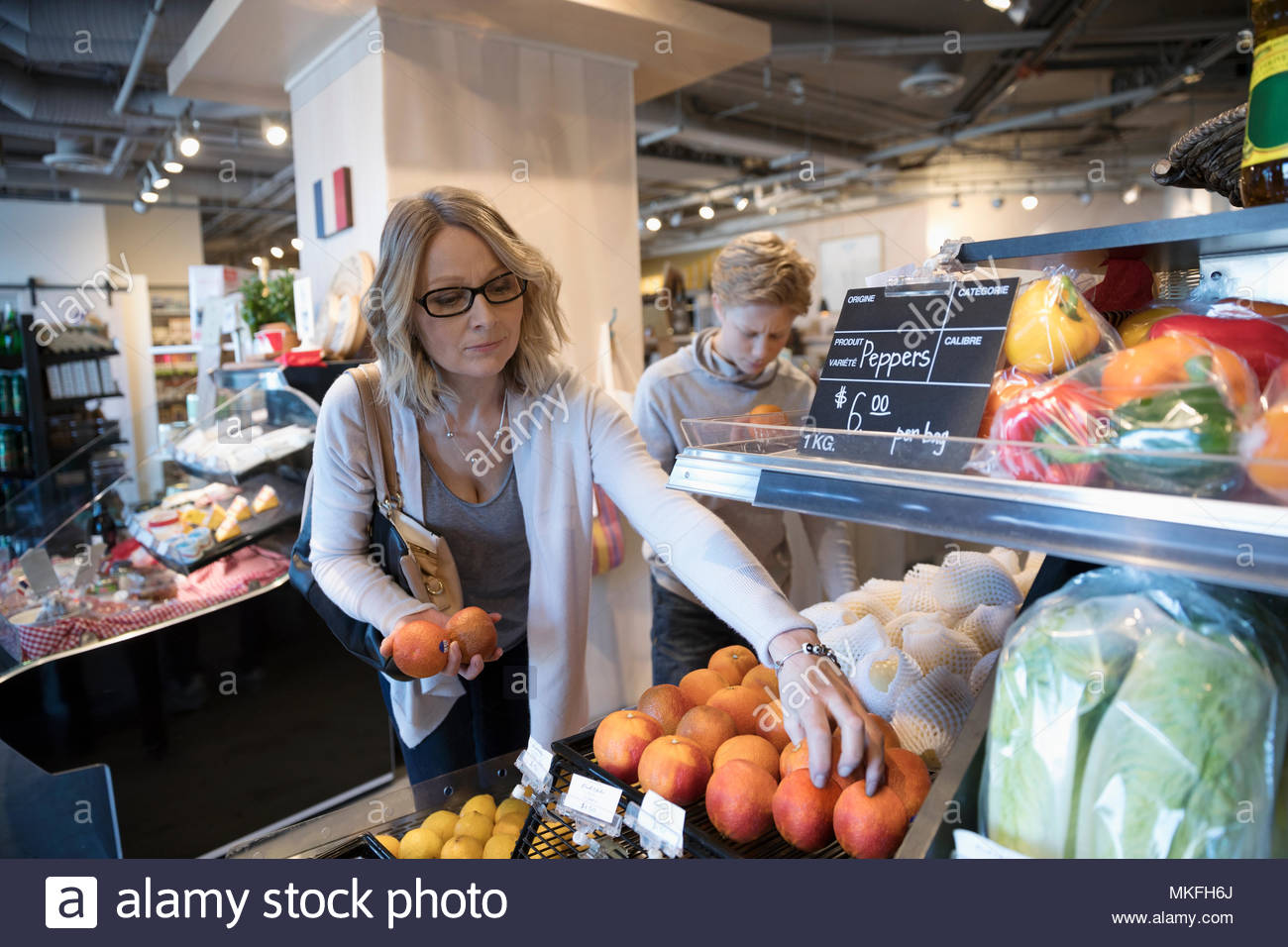 Woman grocery shopping, picking out oranges in market - Stock Image