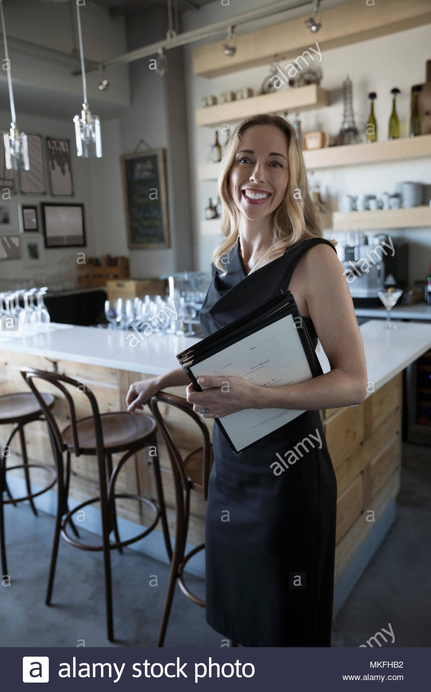 Portrait confident female small business owner with menus in cafe - Stock Image