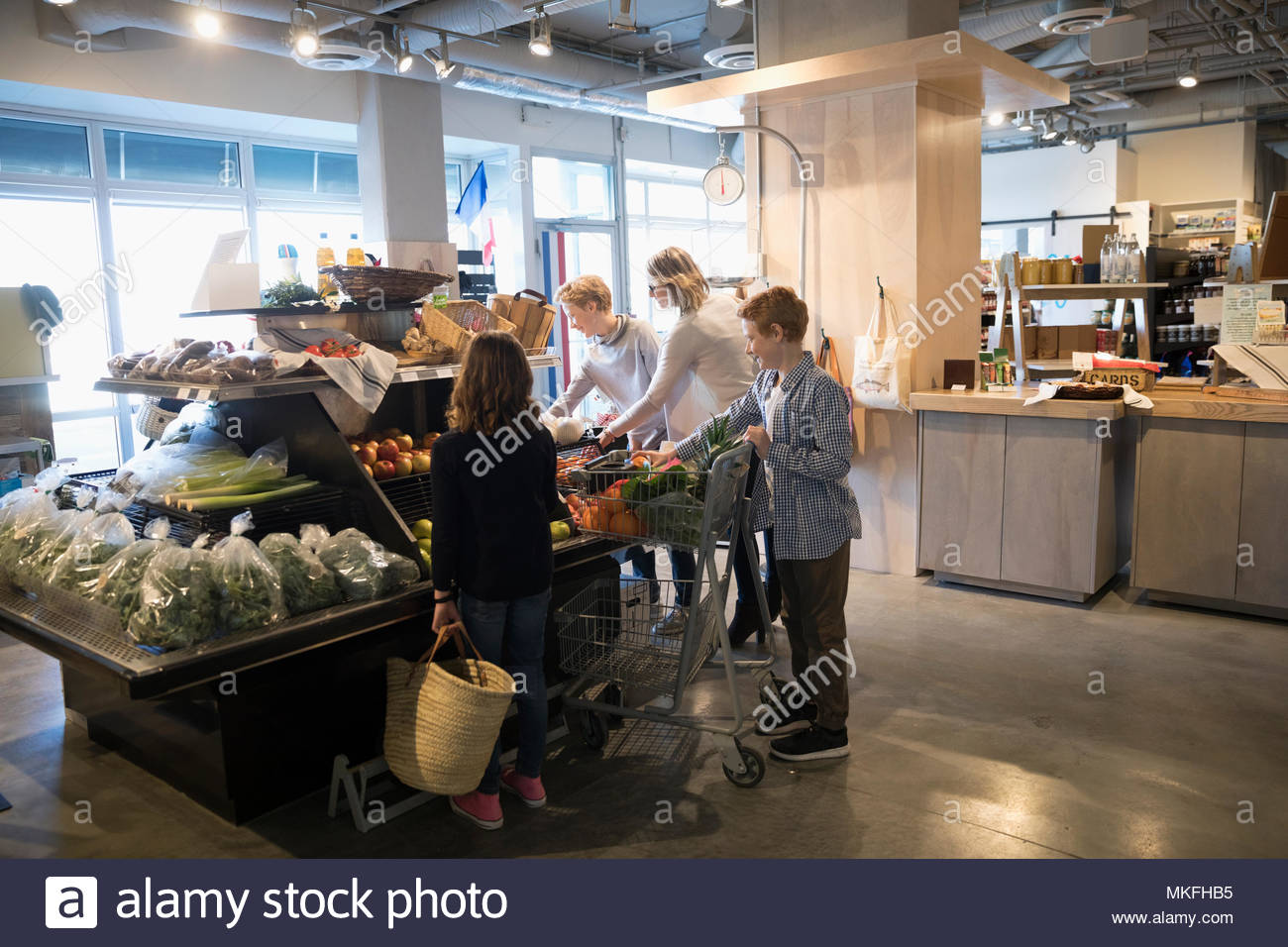 Family grocery shopping, picking out produce in market - Stock Image