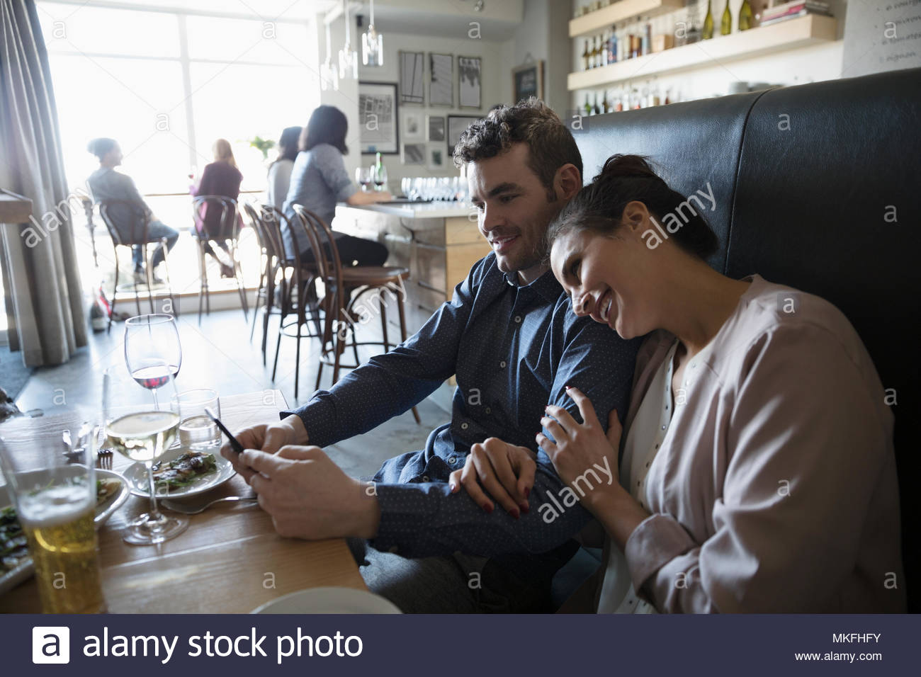Affectionate young couple with smart phone at bar table - Stock Image