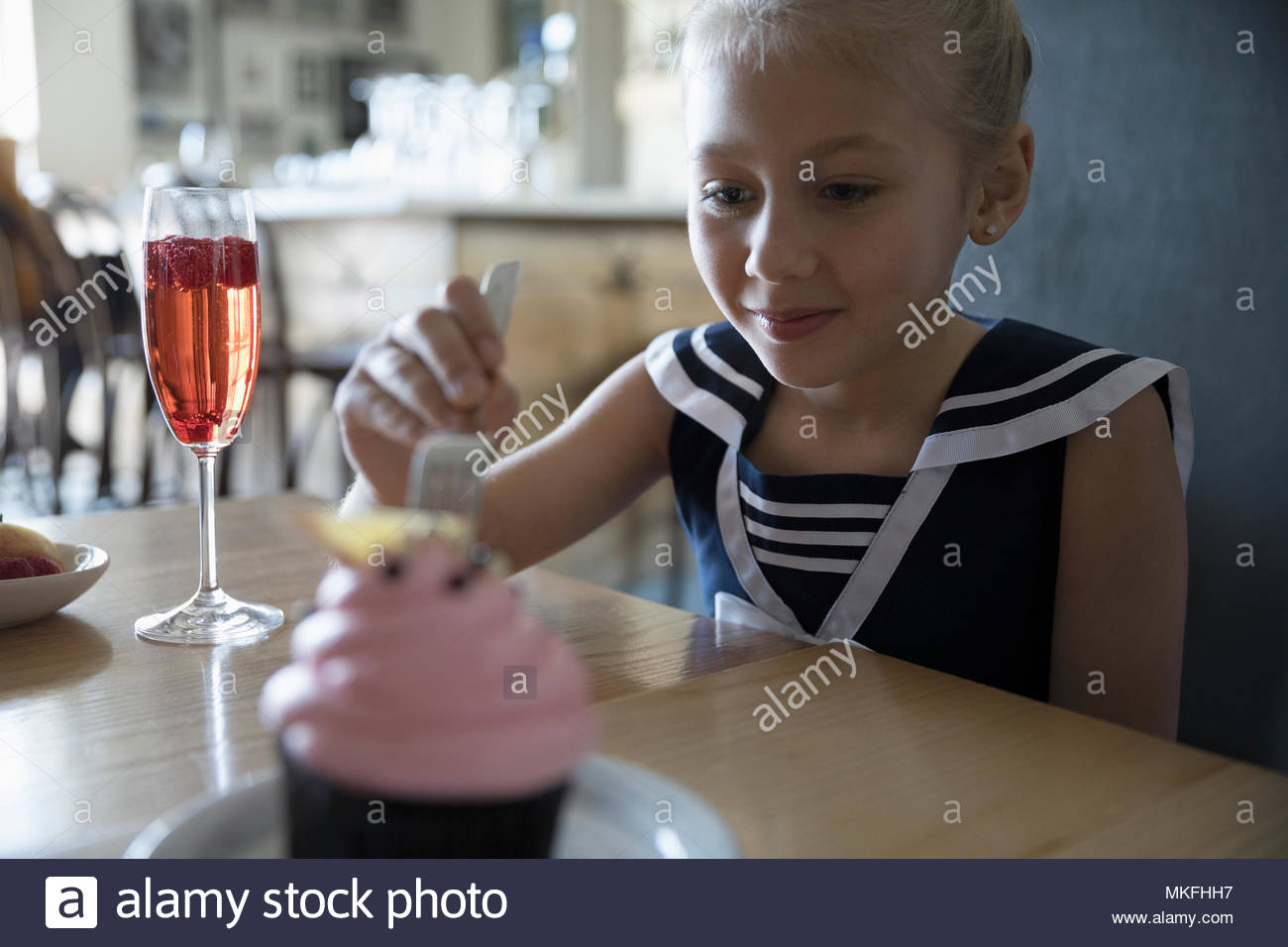 Eager girl celebrating birthday, eating cupcake in cafe - Stock Image