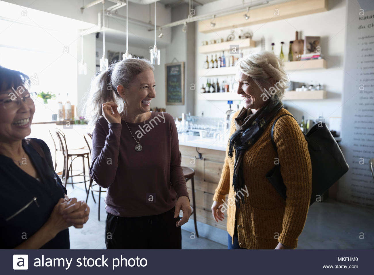Happy senior women friends talking in cafe - Stock Image