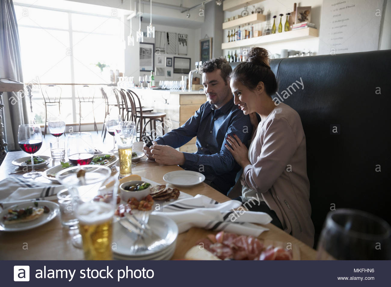 Young couple with smart phone at bar table - Stock Image