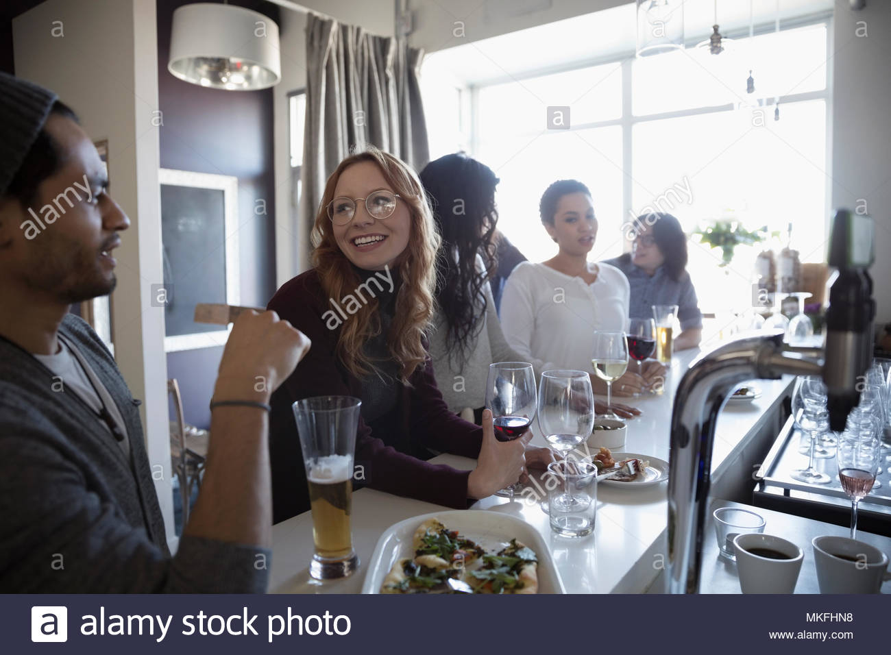 Young friends talking, enjoying happy hour at bar, drinking beer and wine - Stock Image
