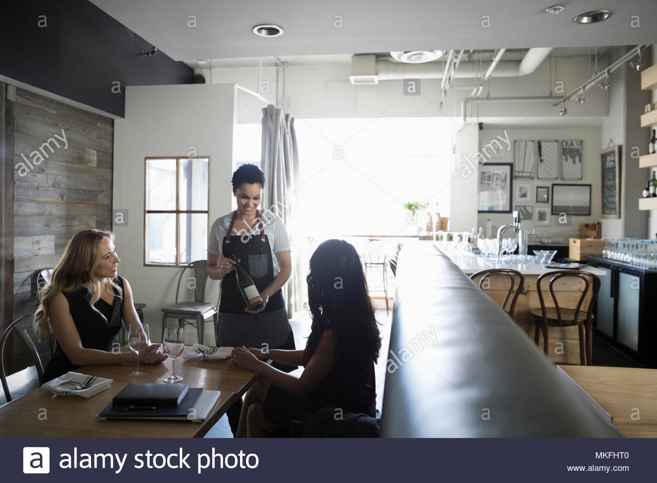 Waitress serving wine to women in cafe - Stock Image