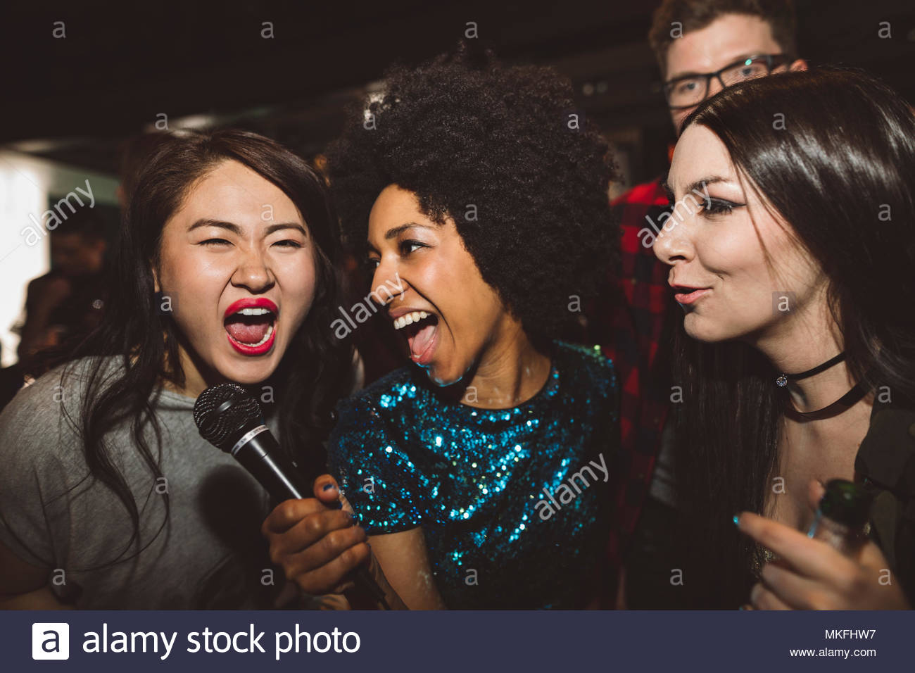 Playful, exuberant young female millennial friends singing karaoke - Stock Image