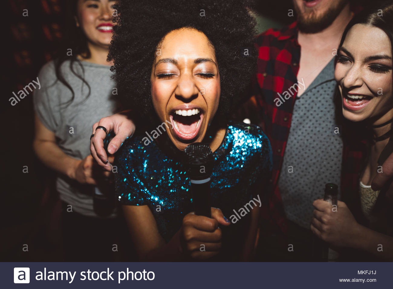 Exuberant young female millennial singing karaoke - Stock Image