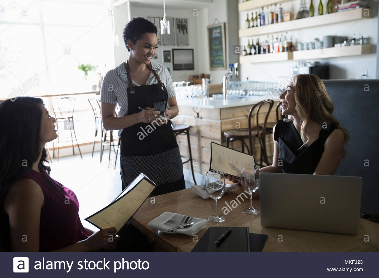 Businesswomen ordering from waitress at cafe - Stock Image