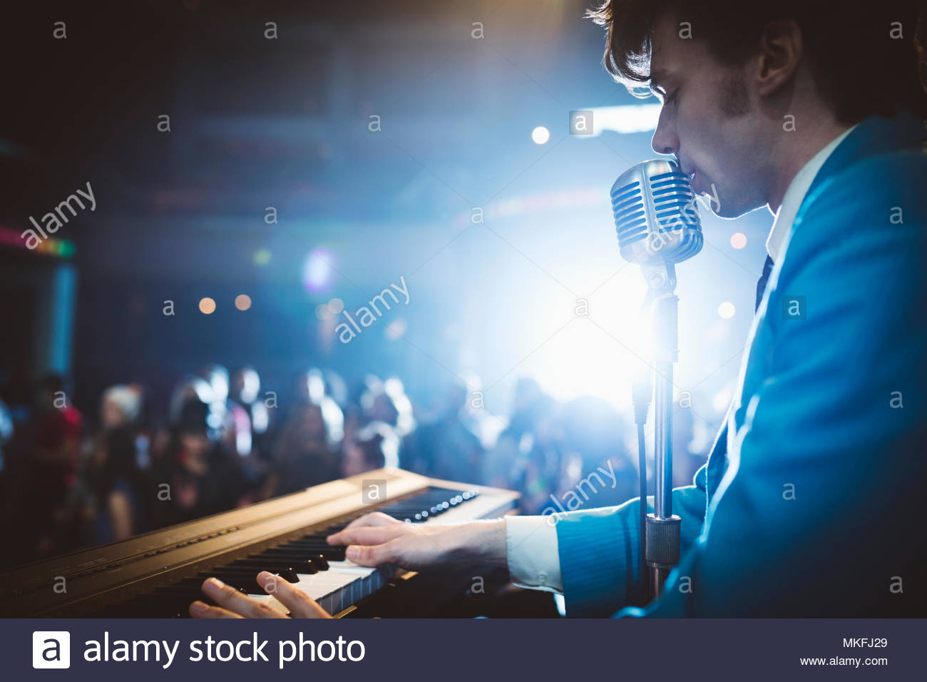 Rockabilly musician playing electric piano and singing into microphone on stage at music concert - Stock Image
