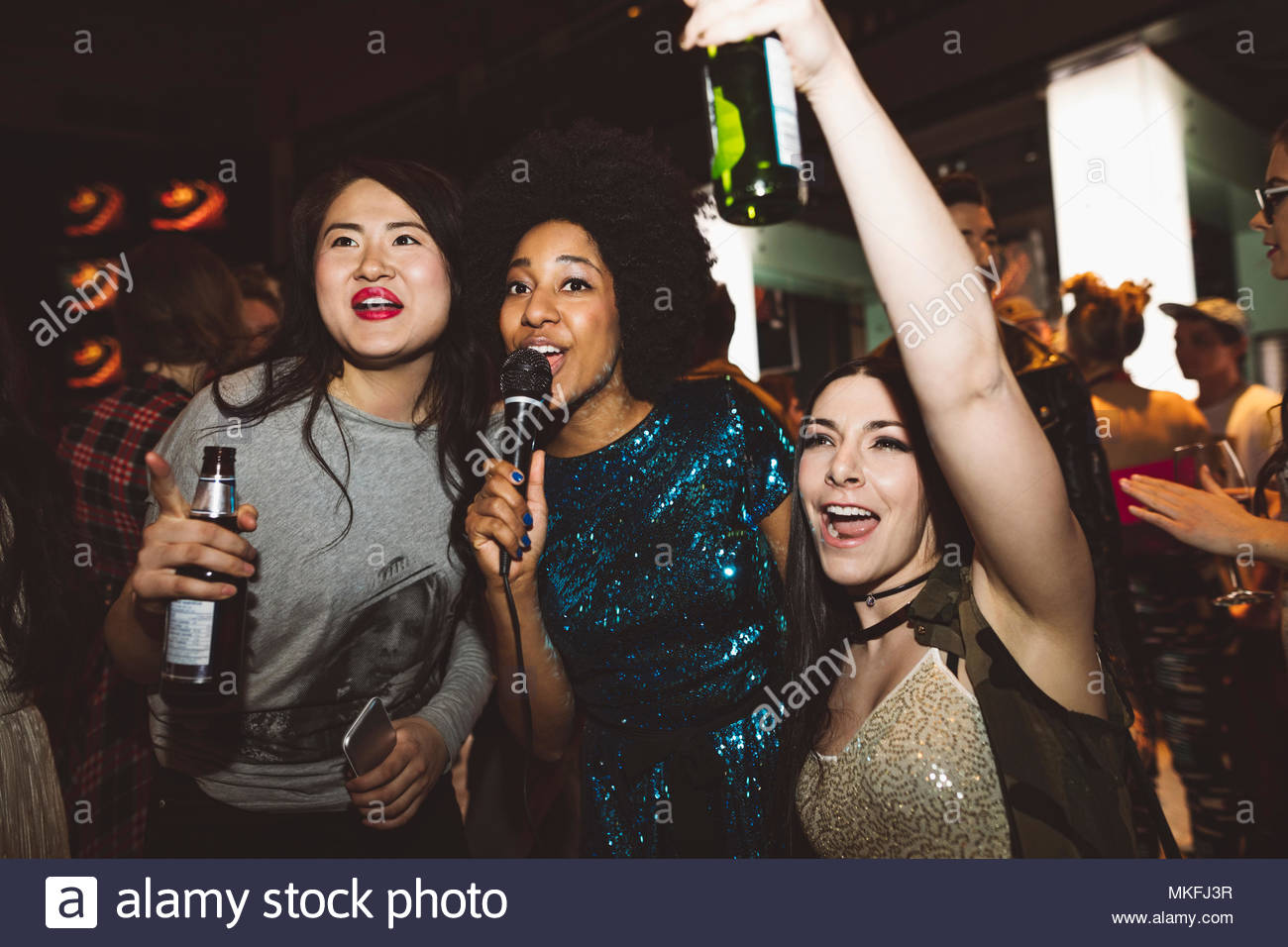 Playful young female millennial friends drinking beer and singing karaoke at nightclub - Stock Image