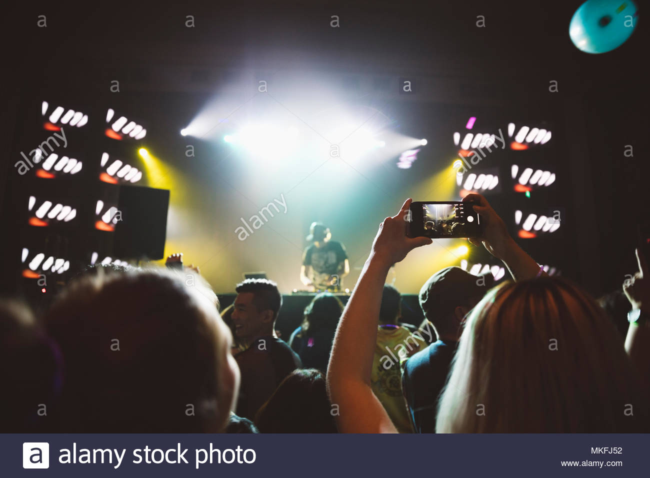 Woman with camera phone in crowd, videoing DJ on nightclub stage - Stock Image