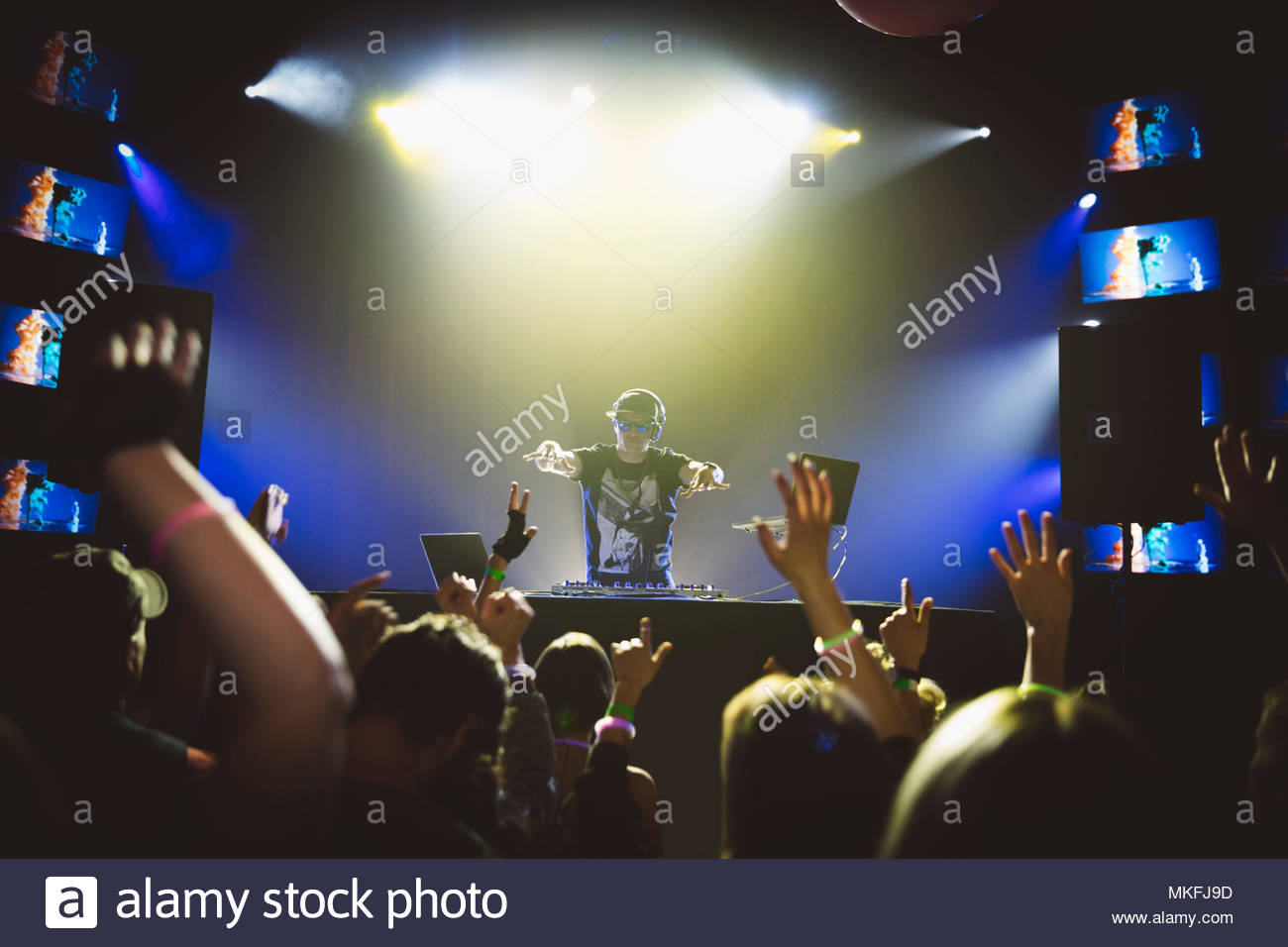 DJ on stage gesturing to crowd dancing in nightclub - Stock Image
