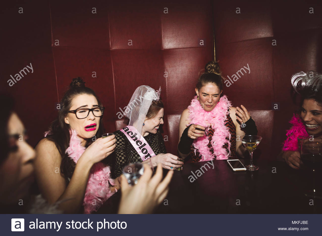Young female millennial friends taking shots at bachelorette party at nightclub - Stock Image