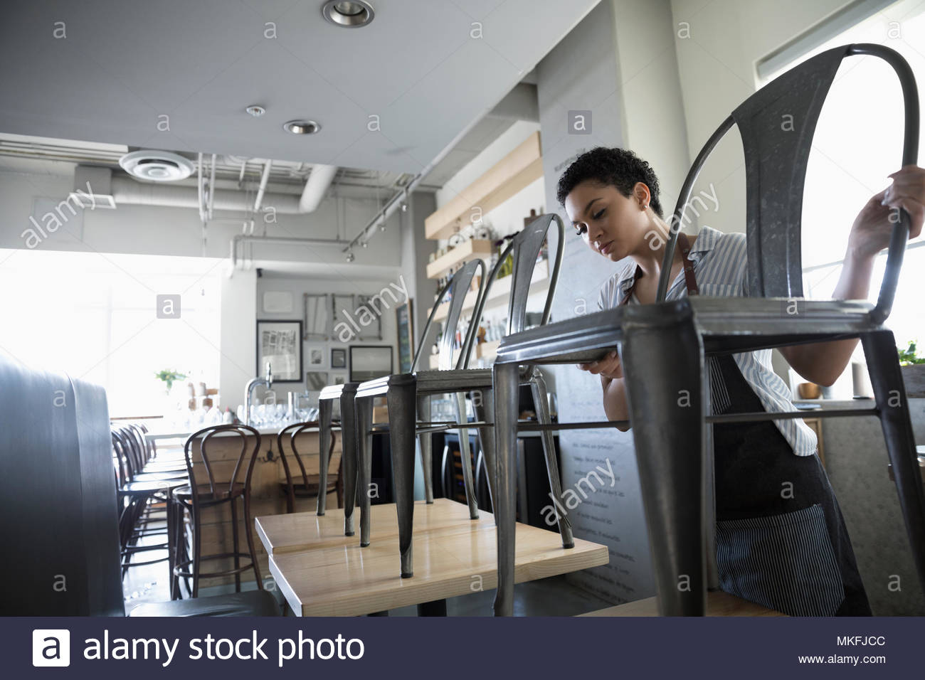 Young woman small business owner stacking chairs on tables in cafe - Stock Image