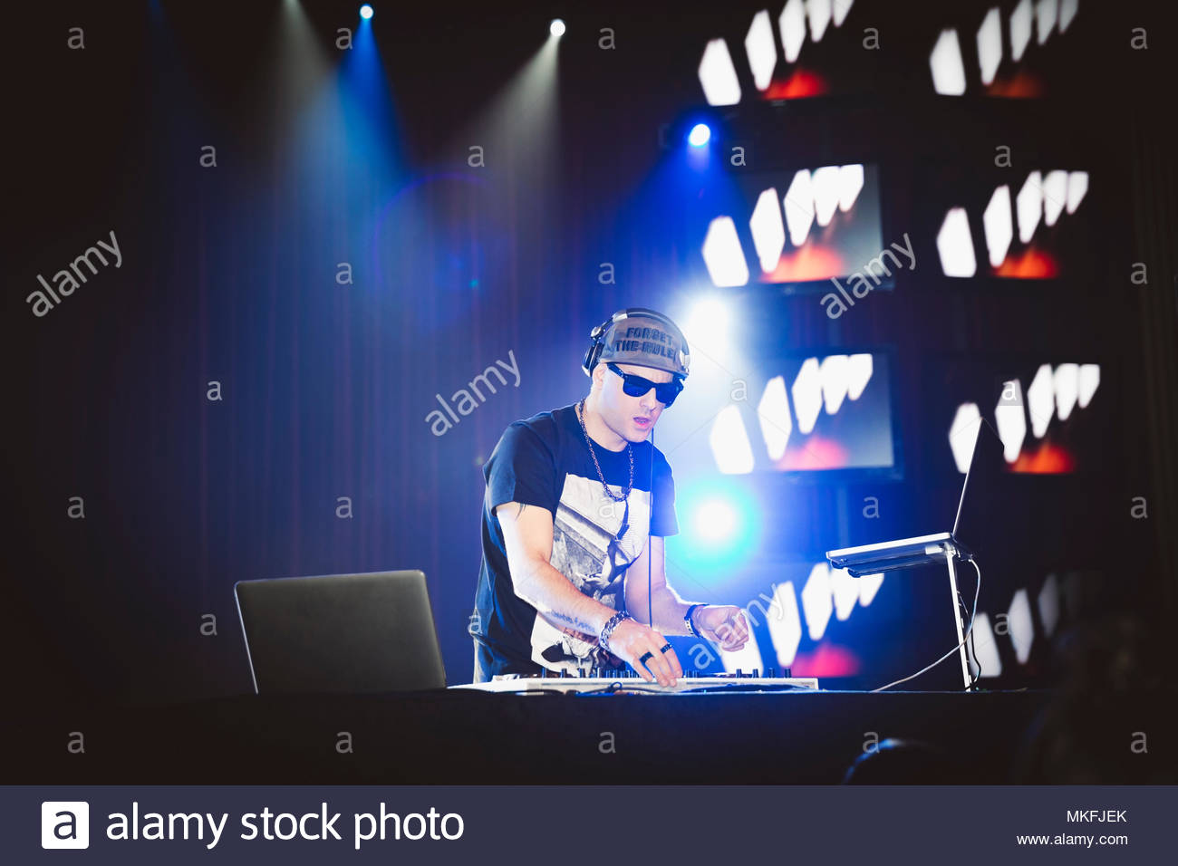 DJ playing music at sound mixer and laptops on nightclub stage - Stock Image