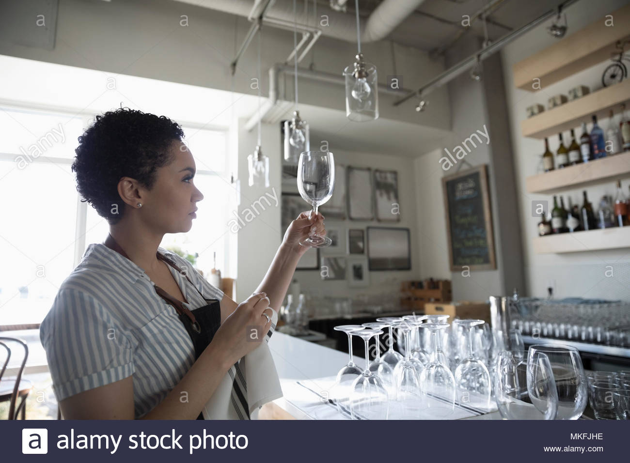 Young woman small business owner drying wine glasses in bar - Stock Image