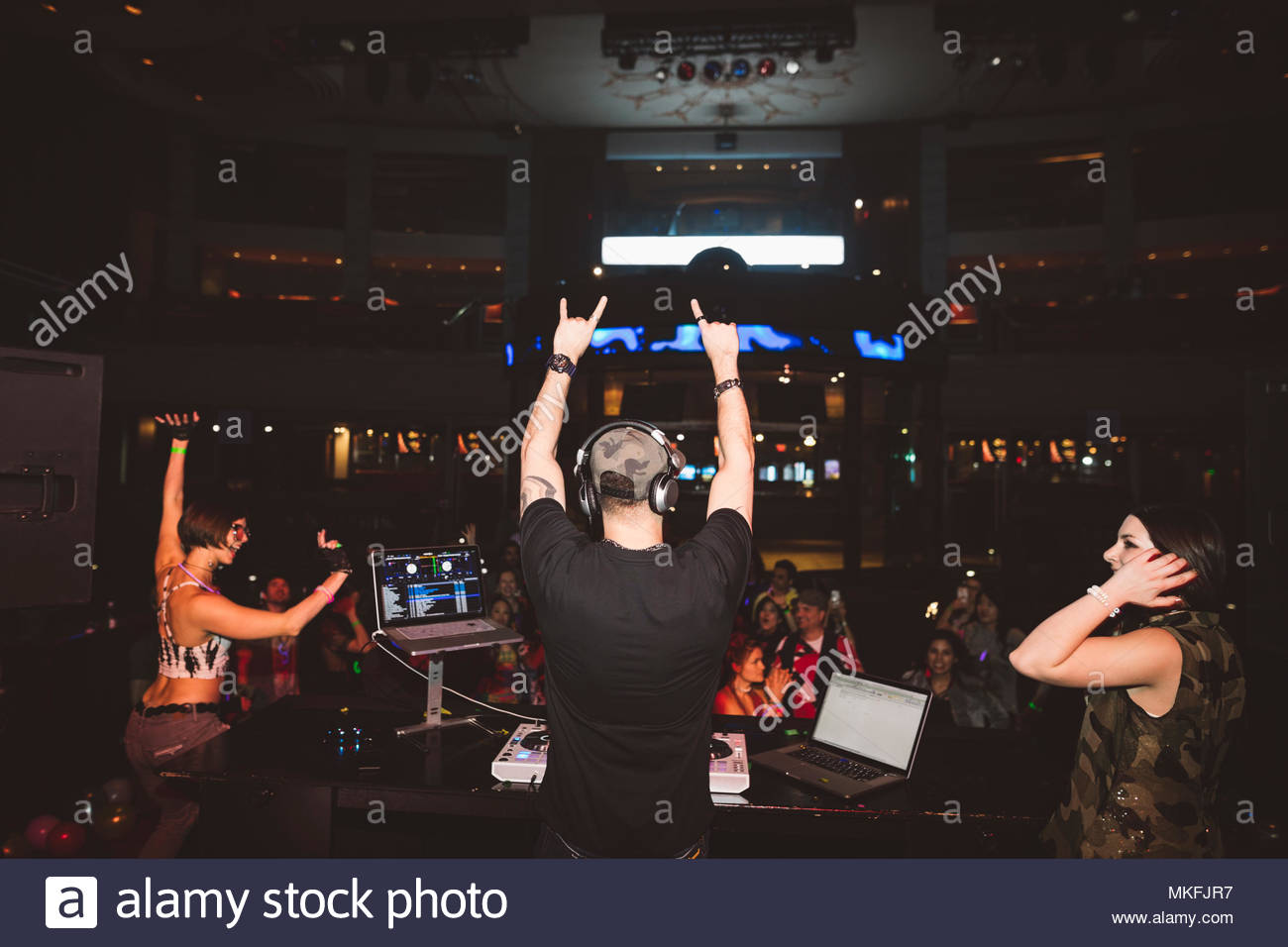 Enthusiastic DJ on stage gesturing to crowd in nightclub - Stock Image