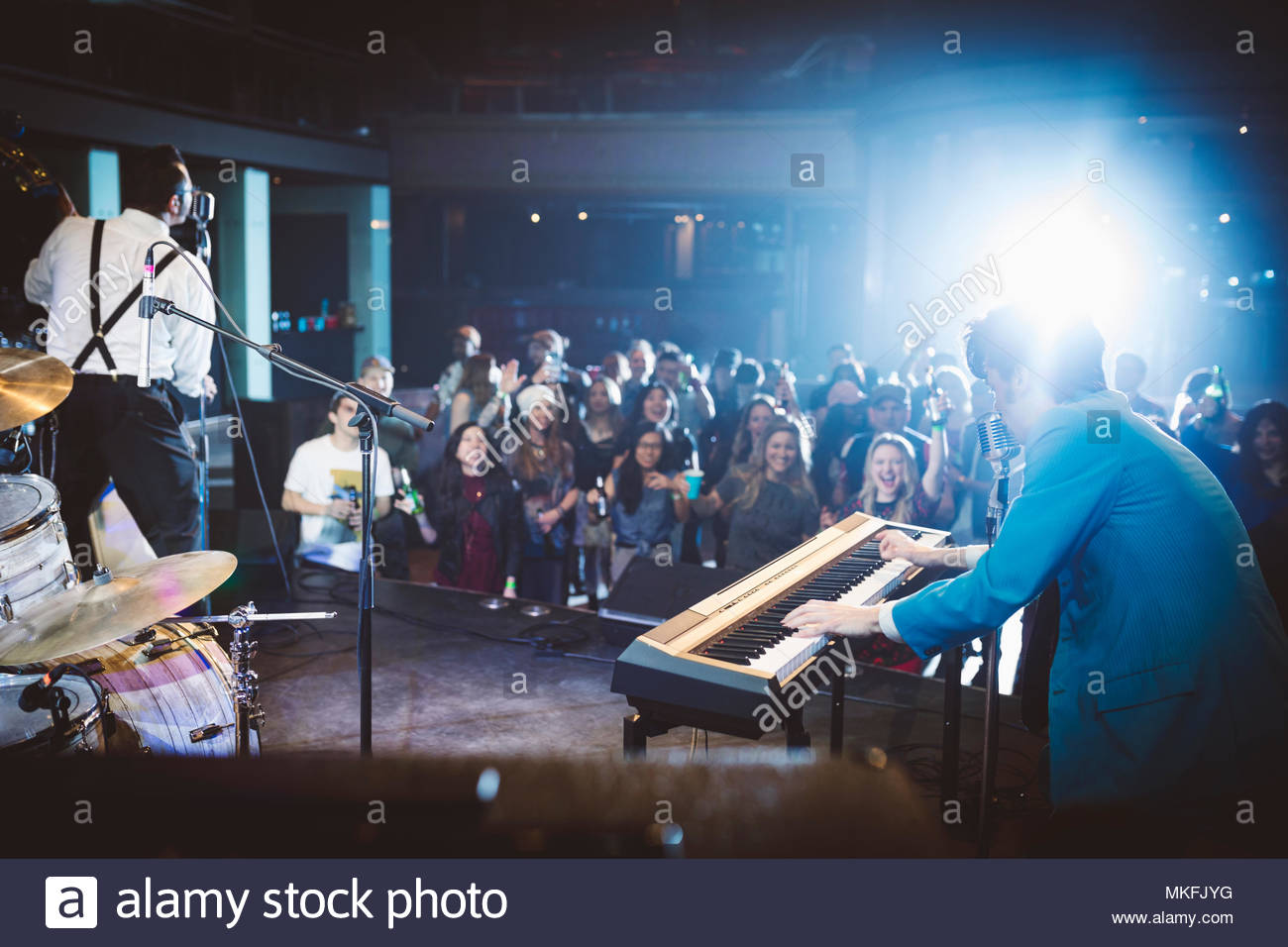 Crowd watching rockabilly musicians perform on stage at music concert - Stock Image