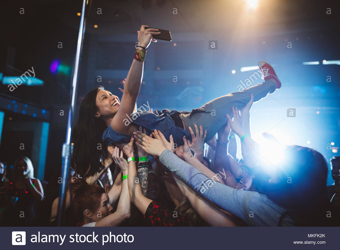 Exuberant woman with camera phone crowdsurfing at music concert in nightclub - Stock Image