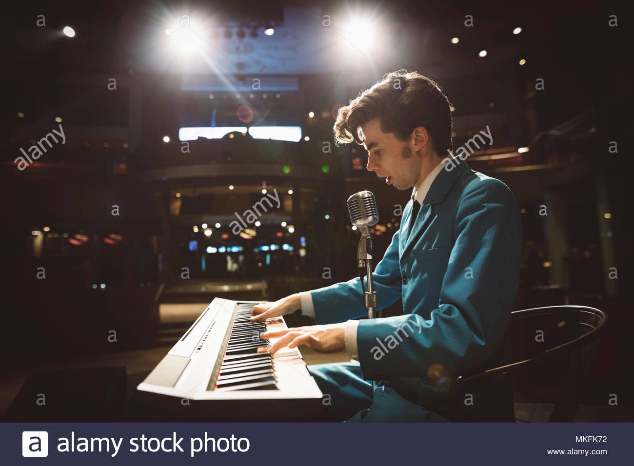 Rockabilly musician playing electric piano on stage - Stock Image