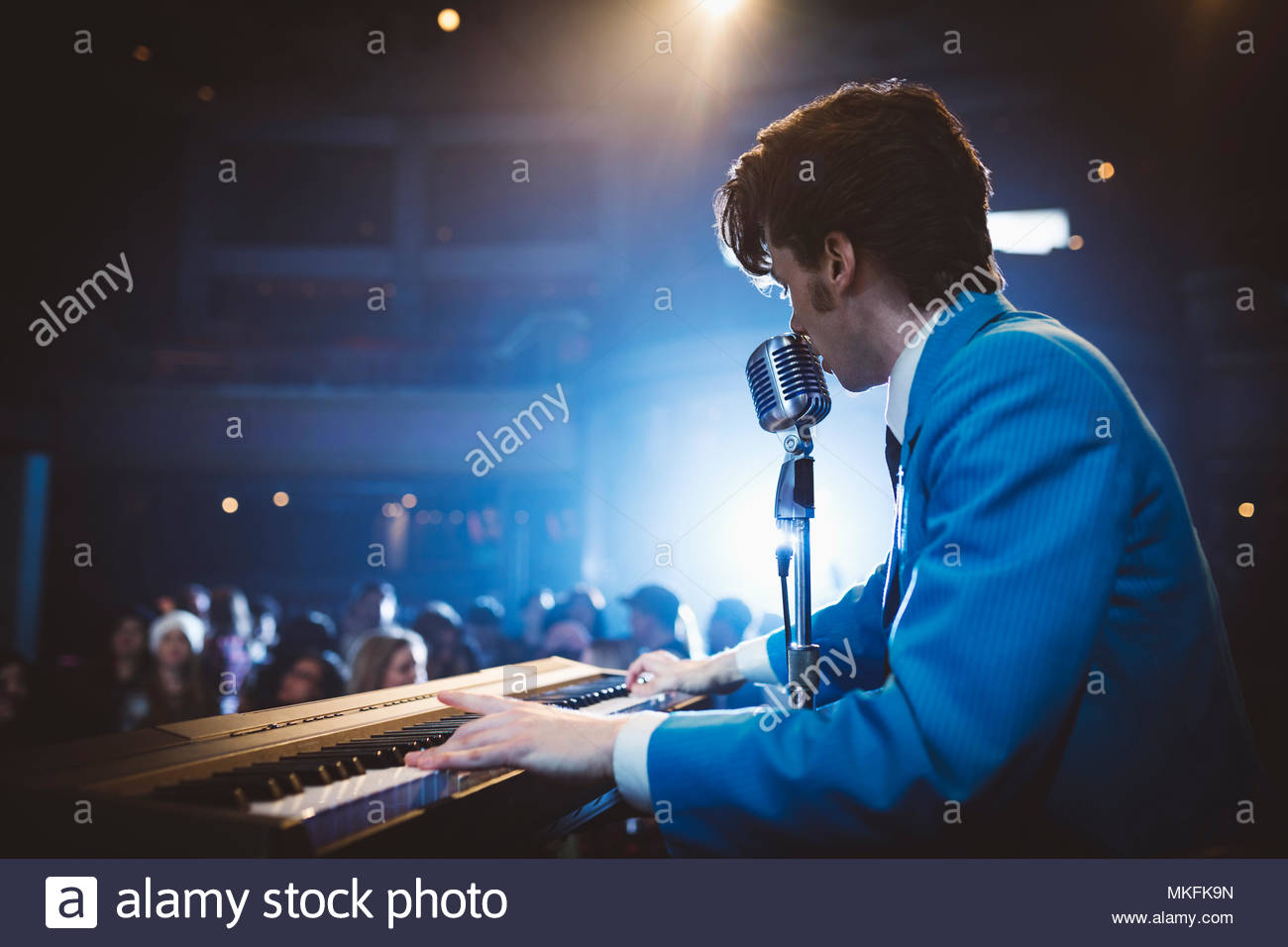 Rockabilly musician playing electric piano and singing into microphone at music concert - Stock Image