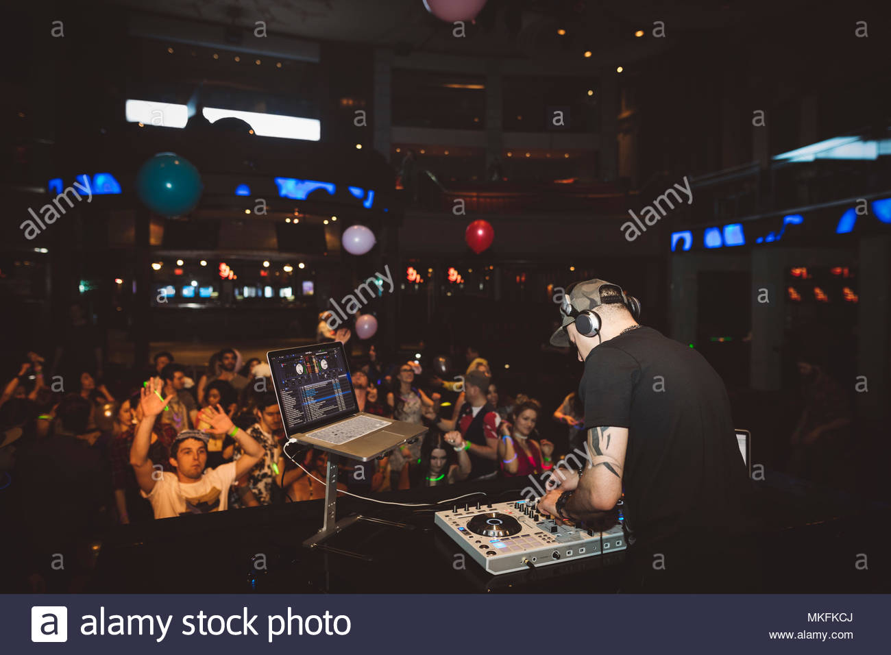 Crowd dancing behind DJ playing music at sound mixer on stage in nightclub - Stock Image
