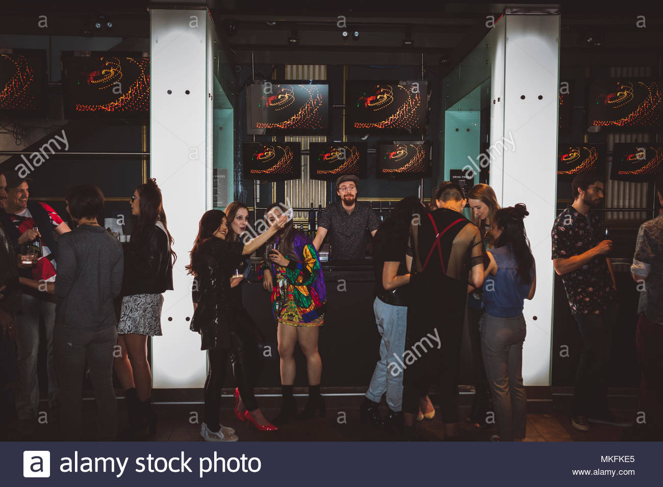 Milennials hanging out, taking selfie in bar - Stock Image