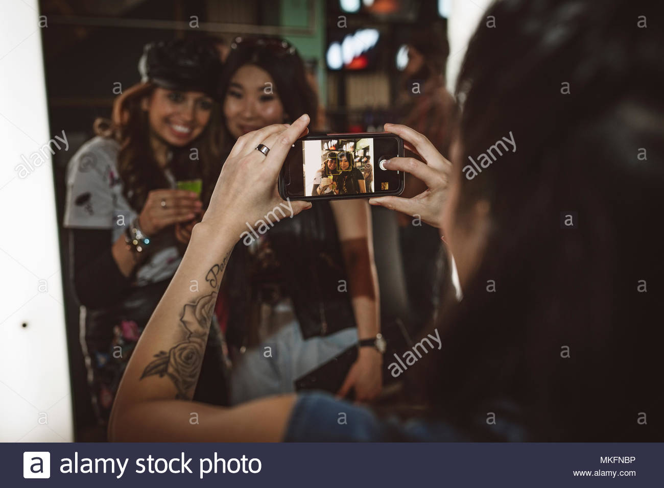 Young female millennial with camera phone photographing friends in nightclub - Stock Image