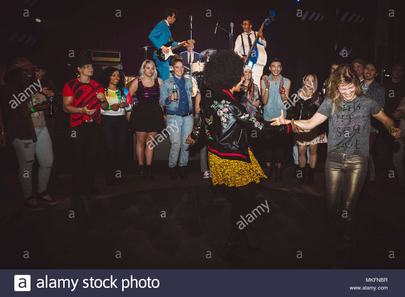 Milennials dancing and partying, enjoying music concert at nightclub - Stock Image