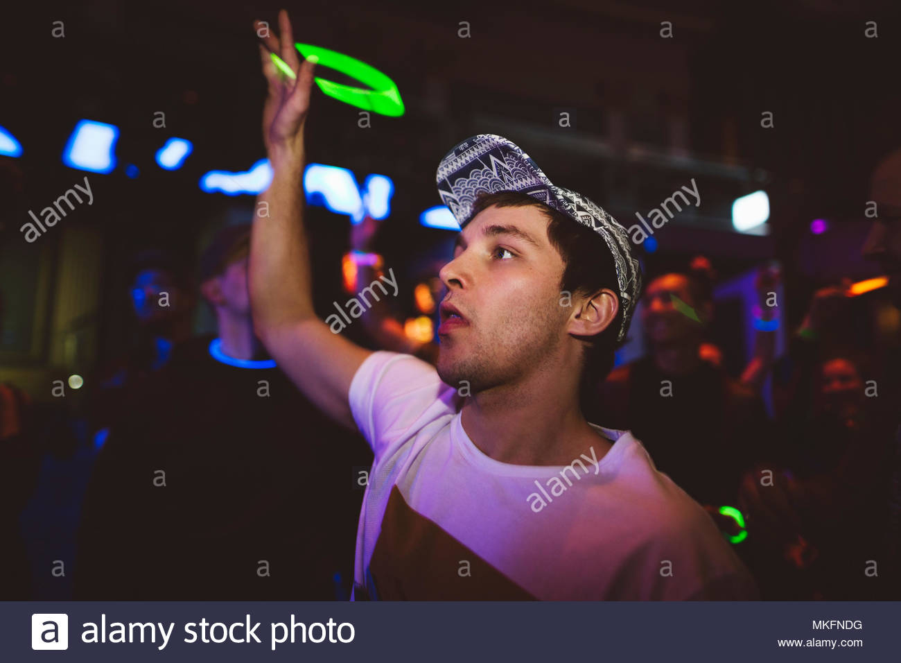 Confident young male millennial dancing, waving neon LED necklace in nightclub - Stock Image