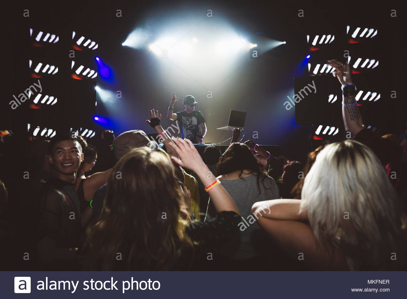 Crowd cheering for DJ performing on nightclub stage - Stock Image