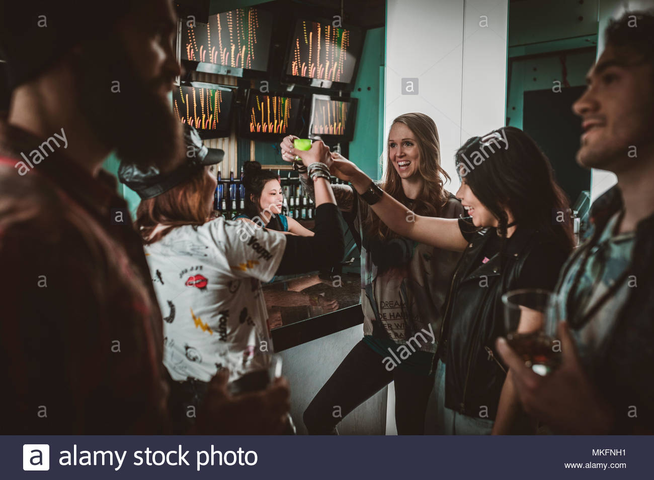 Millennial friends taking shots, partying in nightclub bar - Stock Image