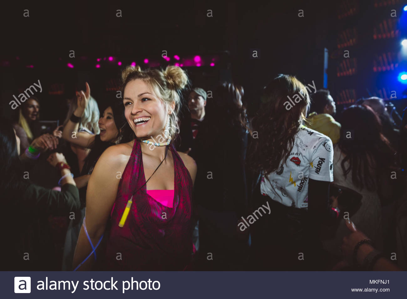 Confident, carefree female millennial dancing and partying in nightclub - Stock Image