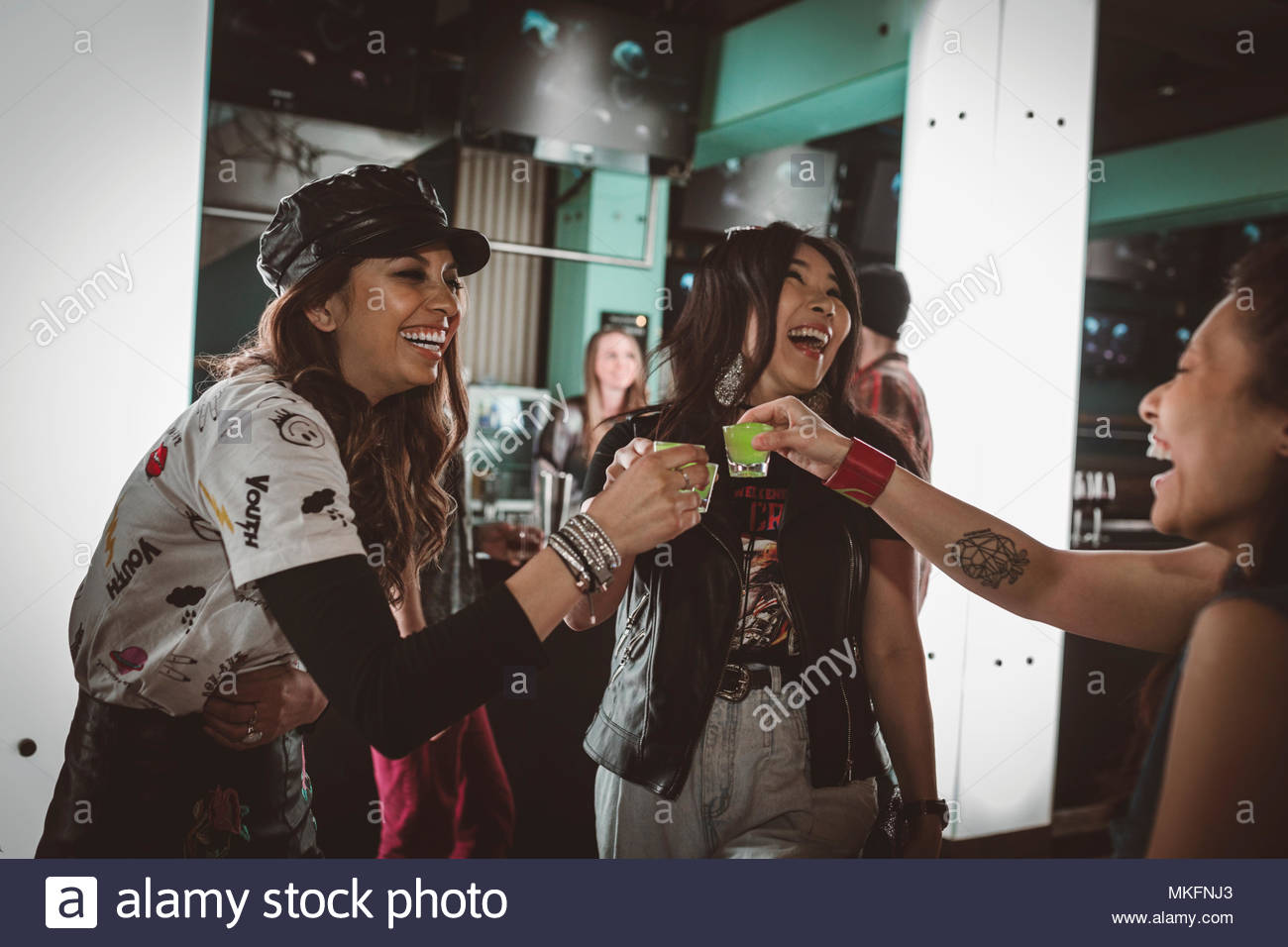 Female millennial friends taking shots, partying in nightclub bar - Stock Image