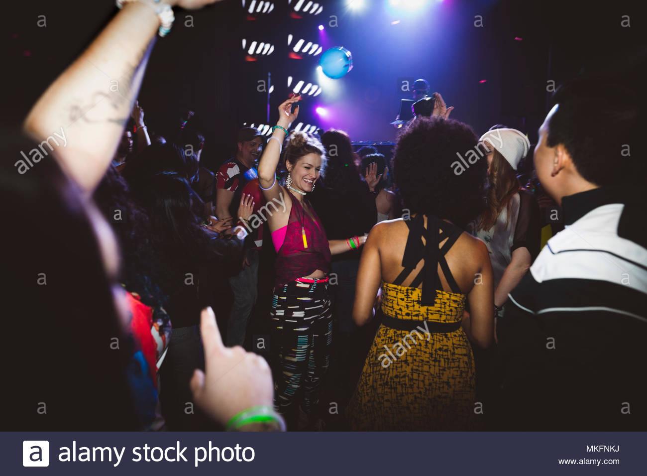 Millennial friends dancing, partying in nightclub - Stock Image