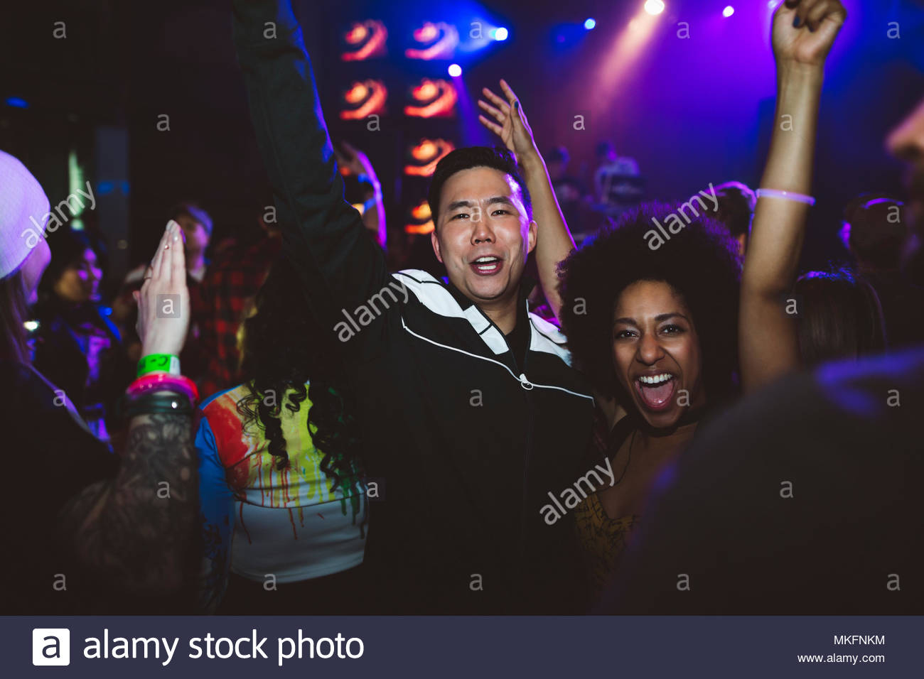 Portrait enthusiastic, fun young millennial couple cheering, dancing in nightclub - Stock Image