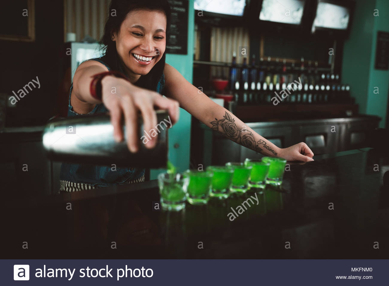 Smiling, happy young female millennial bartender pouring shots at bar - Stock Image
