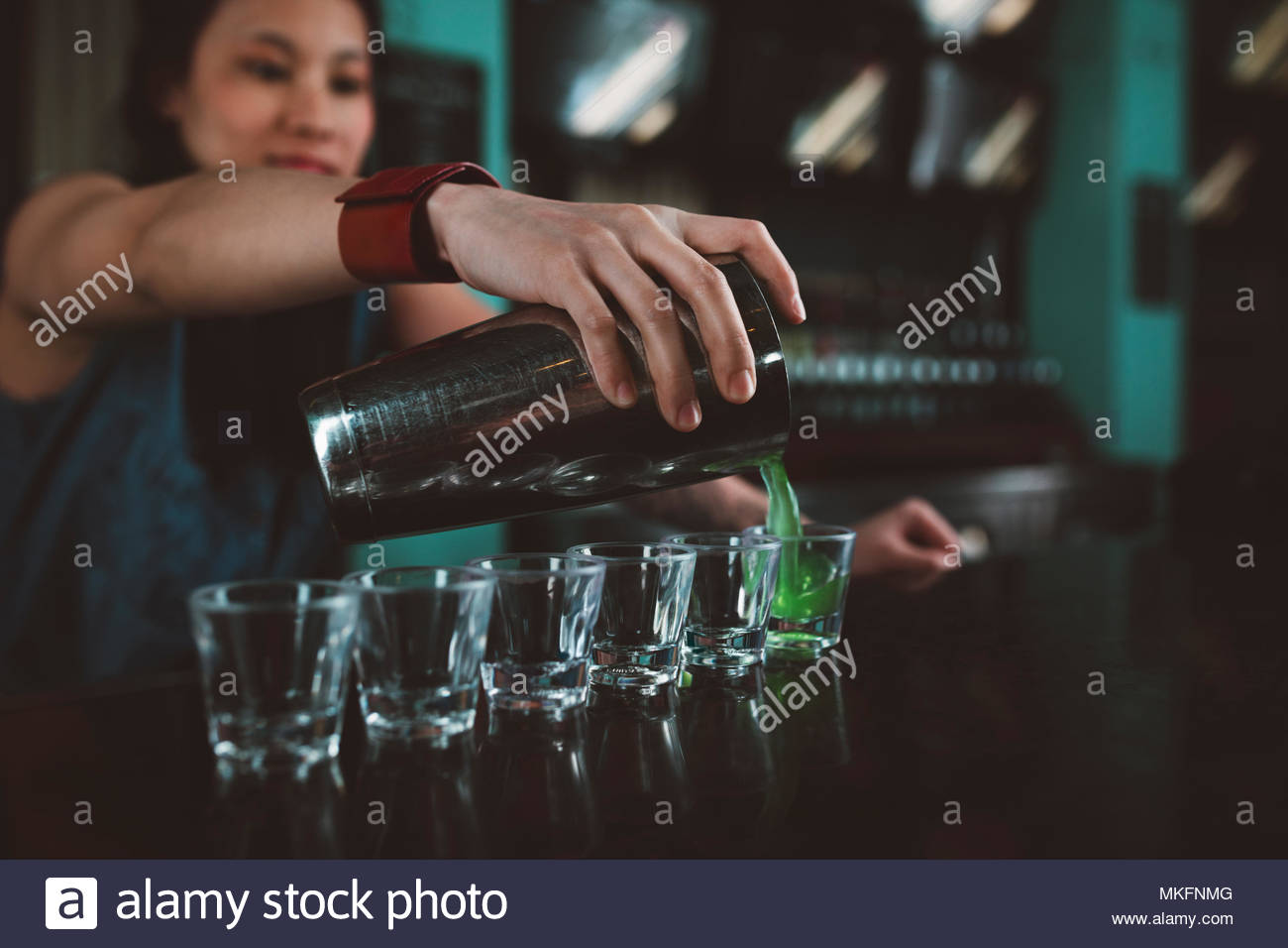 Young female millennial bartender pouring shots at bar - Stock Image