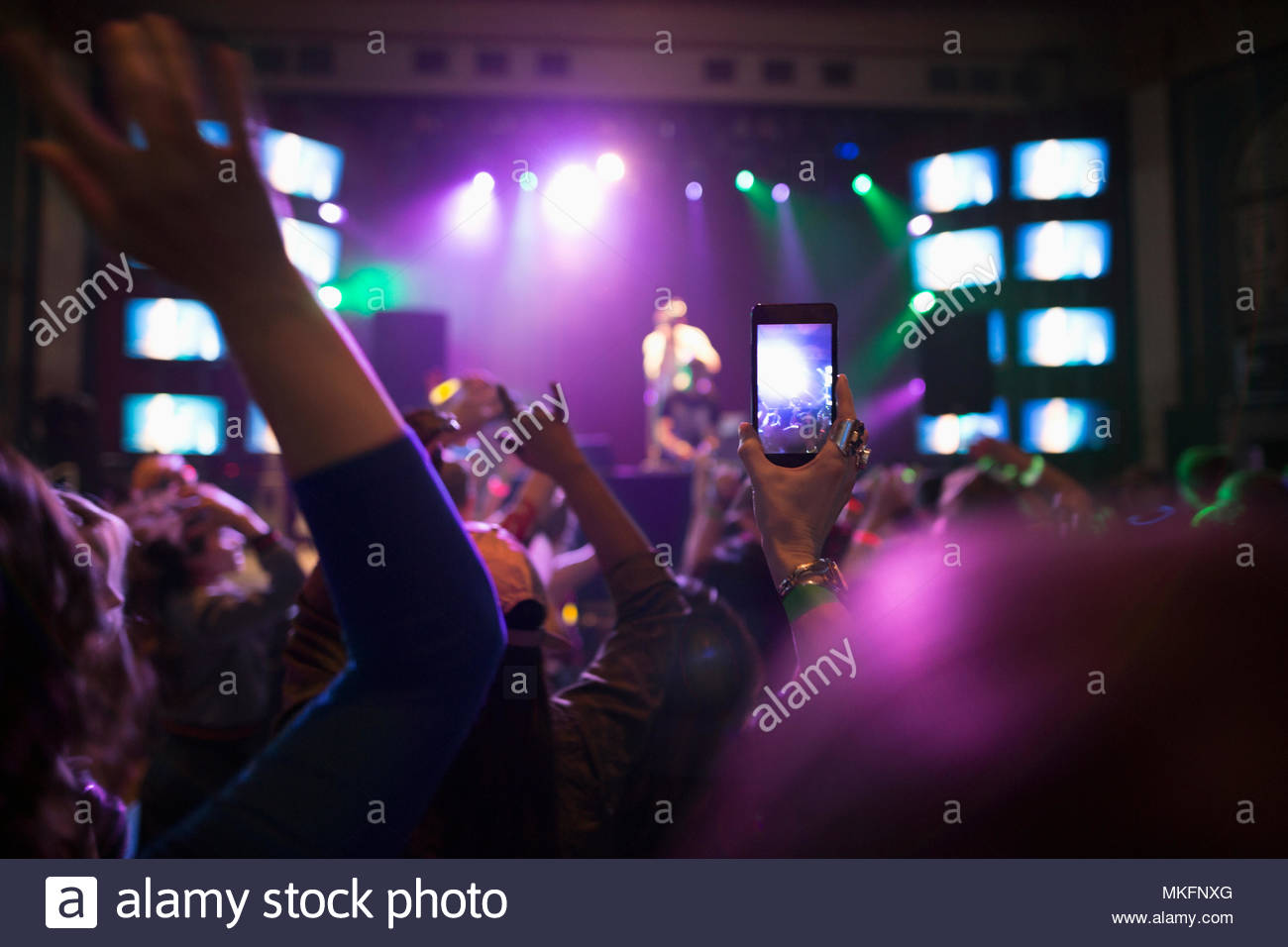 Crowd watching musician perform on nightclub stage, videoing with camera phone - Stock Image
