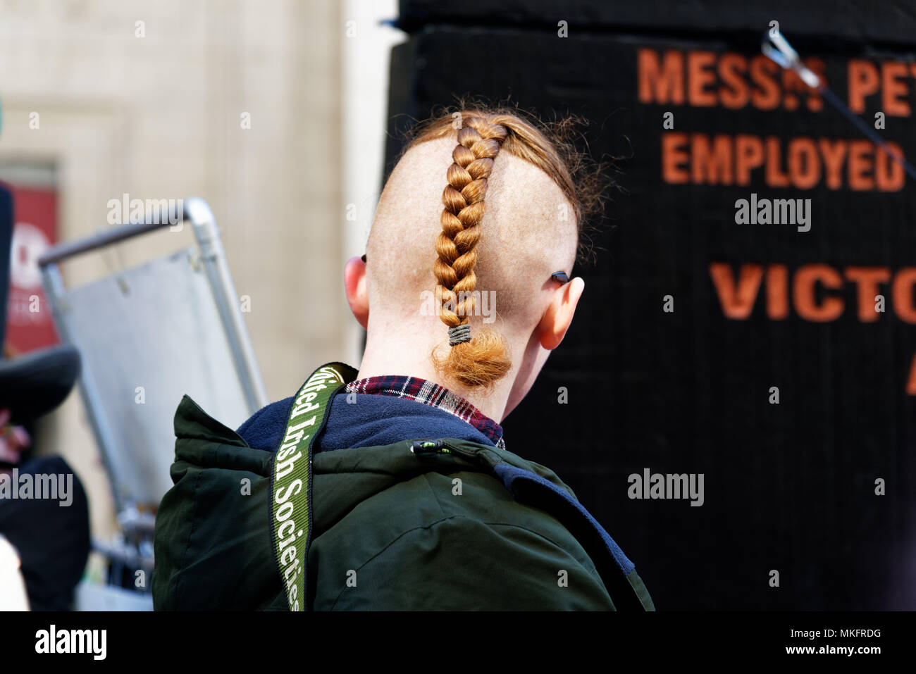 A young man with a Mohican plait at Montreal St Patrick's Day Parade - Stock Image