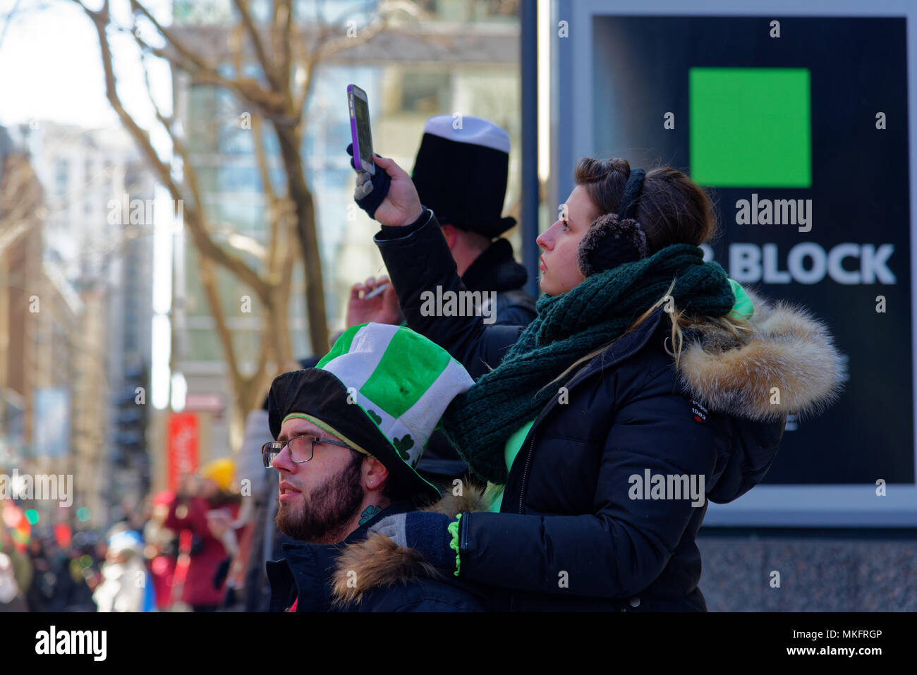 A young woman filming the Montreal St Patrick's Day parade - Stock Image