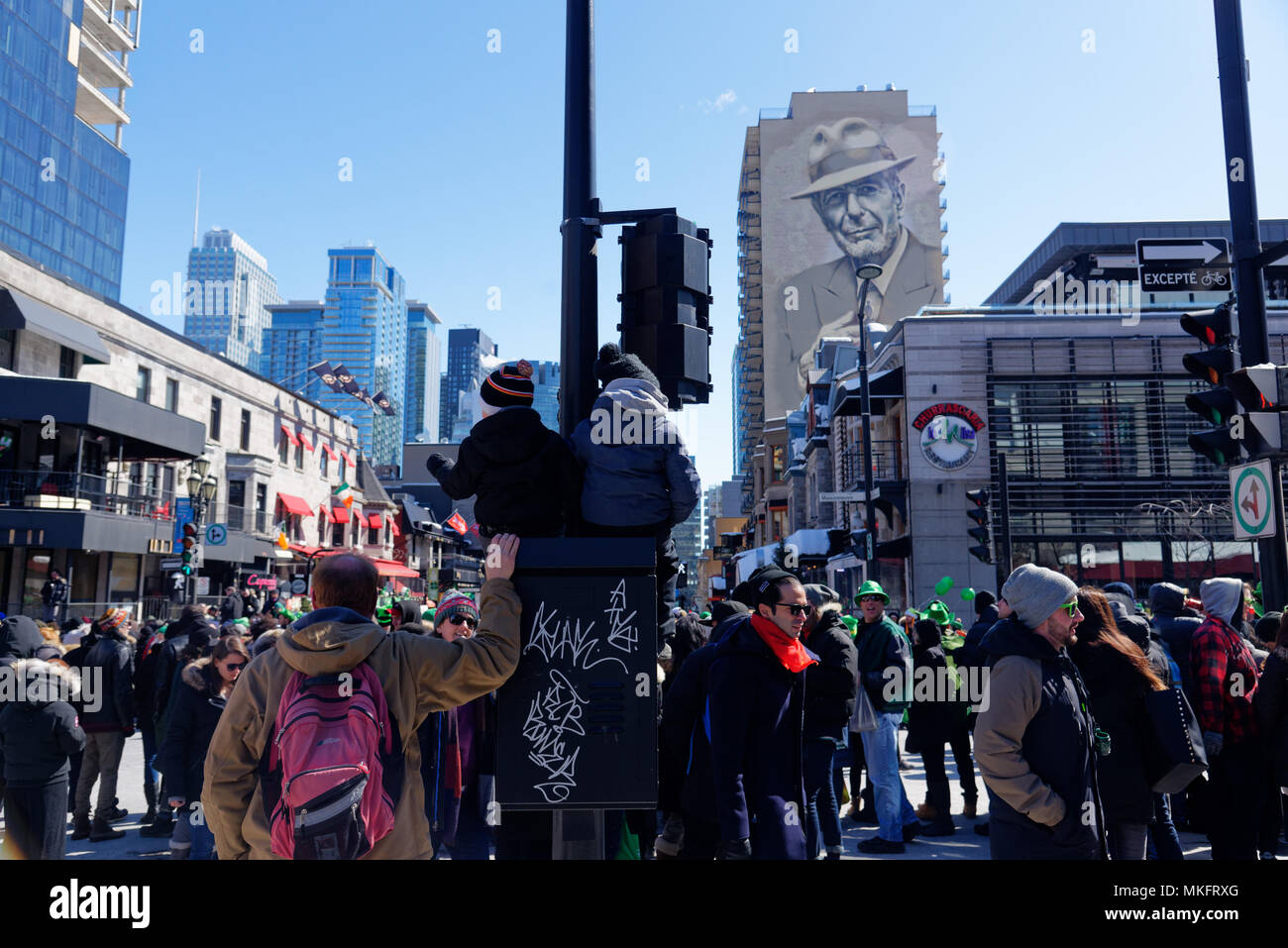 Two children sat up high to watch the St Patrick's Day parade in Montreal - Stock Image