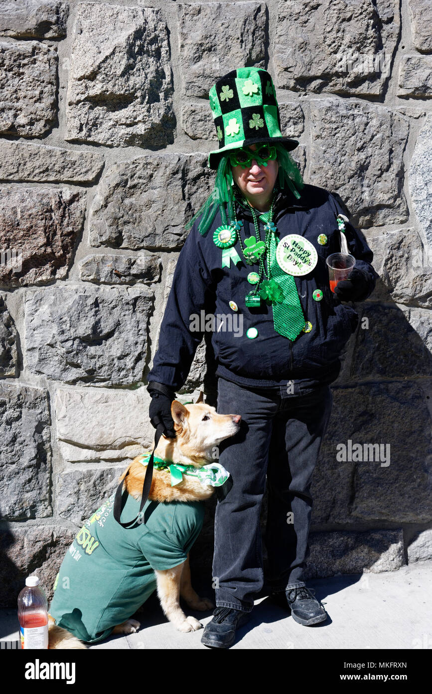 A man and his dog, both wearing green for the Montreal St Patrick's Day parade - Stock Image