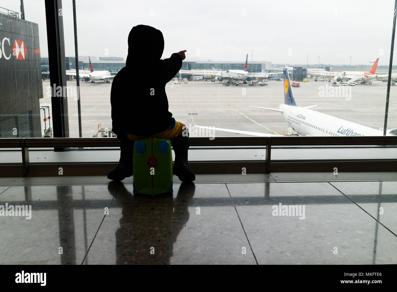A young boy (5 yr old) sat on his suitcase looking at the planes at Heathrow airport - Stock Image