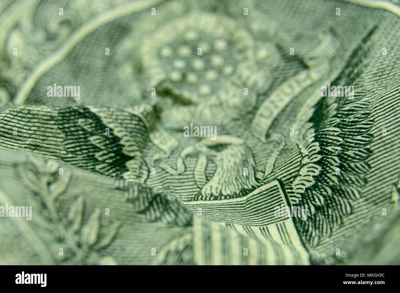 US Dollar Wrinkled Shallow Focus American Coat of Arms - Stock Image